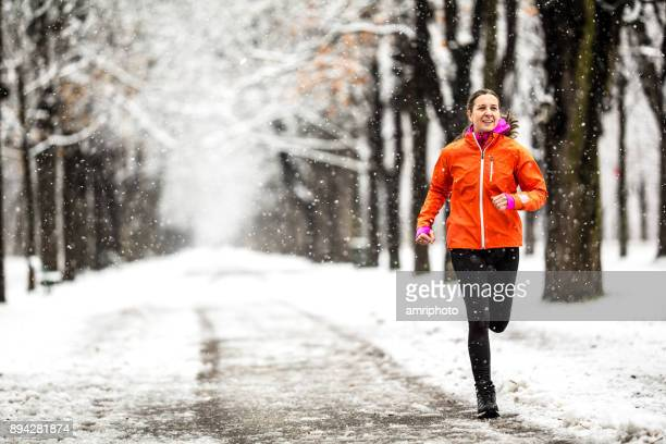 winter breaks - 40 years old woman running on country road through alley on cold winter day with snow and frost - winter stock pictures, royalty-free photos & images