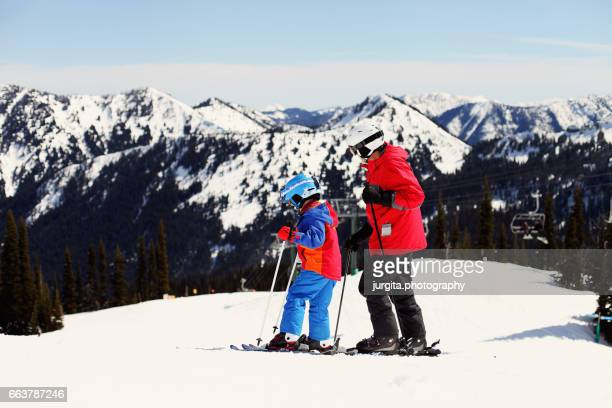 Winter breaks. Father and young child skiing