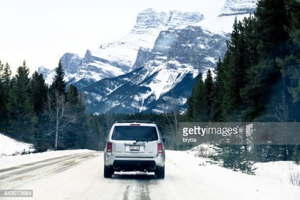 Winter-Pauschalen: Rückansicht des ein SUV Honda Pilot 4WD Fahrt auf einer Winter-Straße in Banff, Banff Nationalpark, Alberta, Kanada