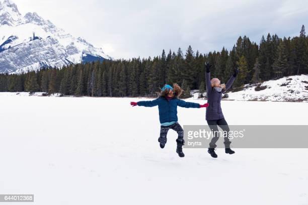Invierno escapadas: caucásico madre e hija divertirse mientras que hacer un salto con los brazos hacia arriba y los brazos estiran, en un helado y la nieve cubren Johnson lago en Banff, Parque nacional Banff, Alberta, Canadá