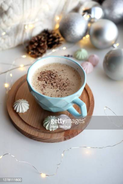 winter christmas picture of blue cup of hot drink coffee with sweet food and fairy lights on the window sill. cosy home details concept. - coffee drink stock pictures, royalty-free photos & images