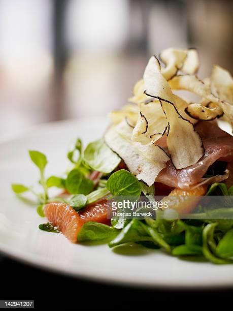 winter citrus salad topped with salsify chips - paire photos et images de collection