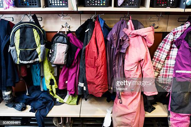 winter coats and backpacks in wardrobe at kindergarten - coat stock pictures, royalty-free photos & images