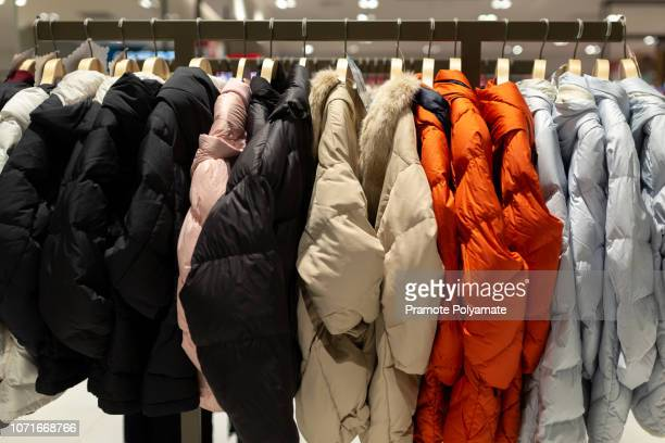 winter coats on a clothes rack in the department store. - rack stock pictures, royalty-free photos & images