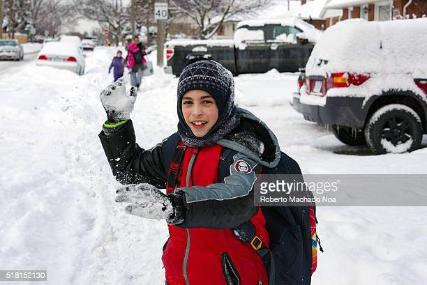 Winter day child going to school Young boy happily throwing snow balls after snow blizzard
