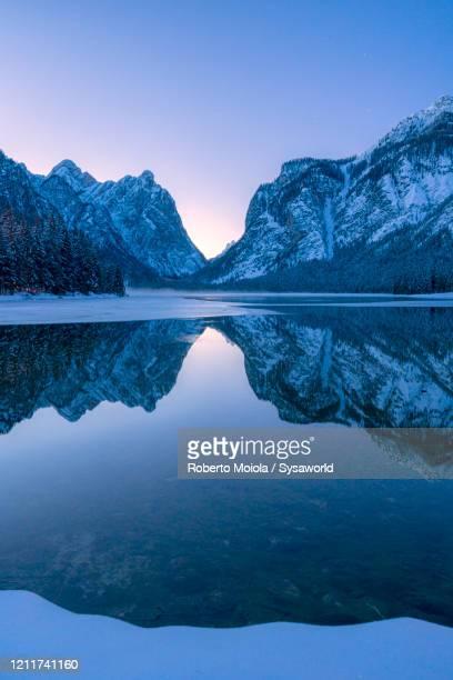 winter dusk over lake dobbiaco, val pusteria, dolomites, italy - 縦位置 ストックフォトと画像