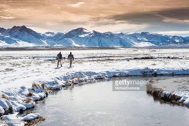 Patta inverno pescatore a piedi attraverso la neve Tundra