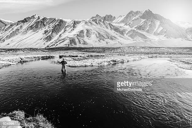 winter fly fisherman with big mountain behind - fly casting stockfoto's en -beelden