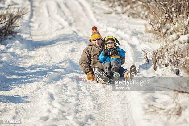 Winter Fun: Grandfather and Grandson Sledding