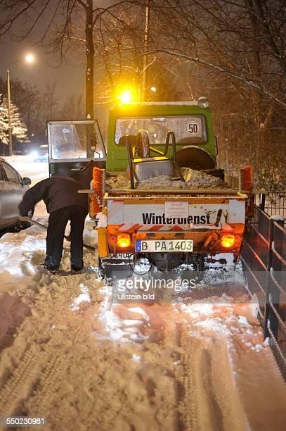 Winter in Berlin - Mitarbeiter eines privaten Winterdienstes versucht sein Fahrzeug in der Storkower Strasse aus dem Schnee zu befreien