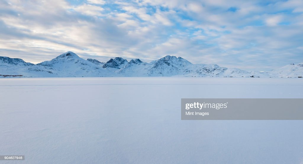 Winter landscape under a cloudy sky, with mountains in the distance. : Stock-Foto