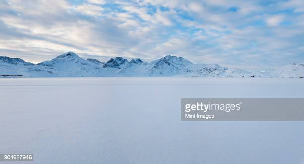 winter landscape under a cloudy sky, with mountains in the distance. - poolklimaat stockfoto's en -beelden