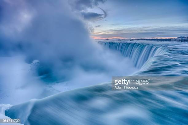 winter landscape with freezing niagara falls at sunrise, ontario, canada - ontario canada ストックフォトと画像