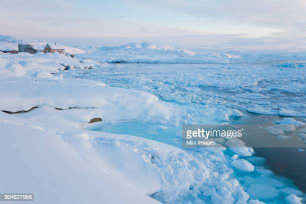 Winter landscape with ice sheets floating on the ocean surface.