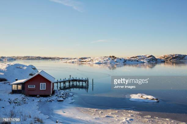 Winter landscape with lake and boat house