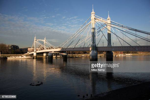 Winter light along the River Thames path on the South side at Battersea looking towards Chelsea over Albert Bridge in London England United Kingdom