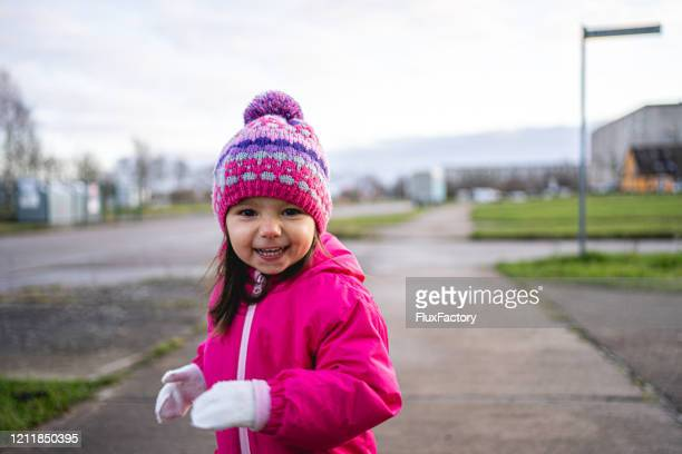 winter morning walk with a little girl - pink coat stock pictures, royalty-free photos & images