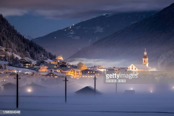 winter night landscape overlooking the austrian tyrolean city of neustift and the pfarre church against the backdrop of mountains and clouds. frosty night with fog in the valley - royal blue stock pictures, royalty-free photos & images