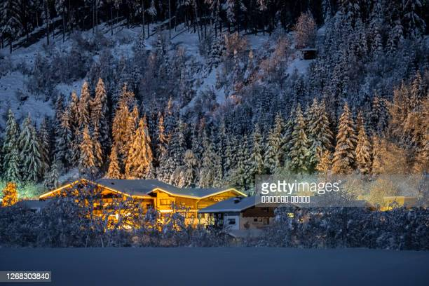 winter night landscape with a view of the austrian tyrolean town of neustift, in the background of fir trees in the snow - royal blue stock pictures, royalty-free photos & images