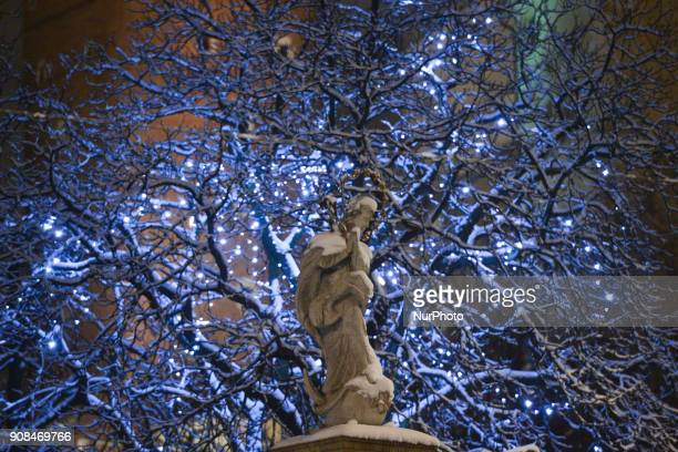 A winter night view of a statue outside of Krakow's Church of St Bernard of Siena On Sunday 21 January 2018 in Krakow Poland