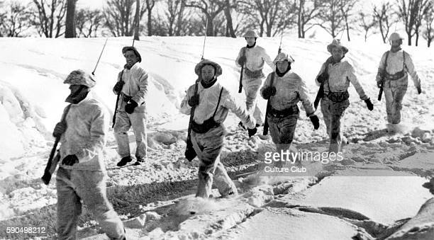 WWII Winter on the Western Front soldiers with bayonets march through the snow Caption reads 'Wearing white camouflage British troops exercise in...