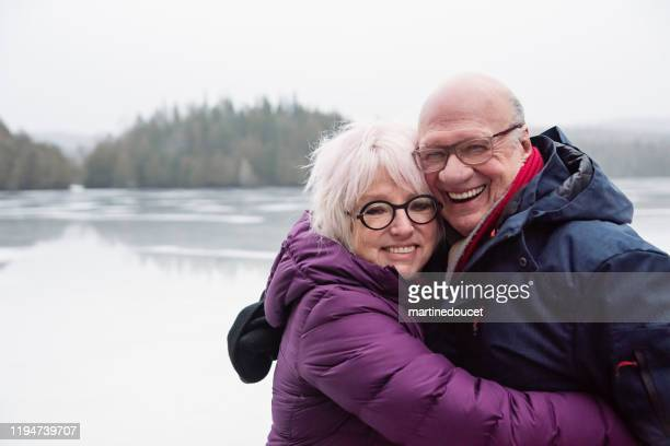 "winter outdoors senior couple portrait by a lake. - ""martine doucet"" or martinedoucet stock pictures, royalty-free photos & images"