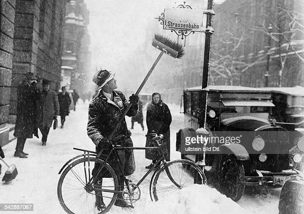 Winter pictures Man with bicycle and broom sweeping snow off a street sign in Berlin 1929 Published by 'Berliner Morgenpost' Vintage property of...