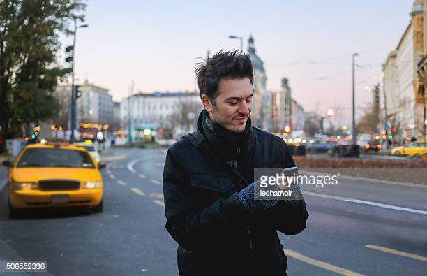 Winter portrait of a man in the city calling taxi