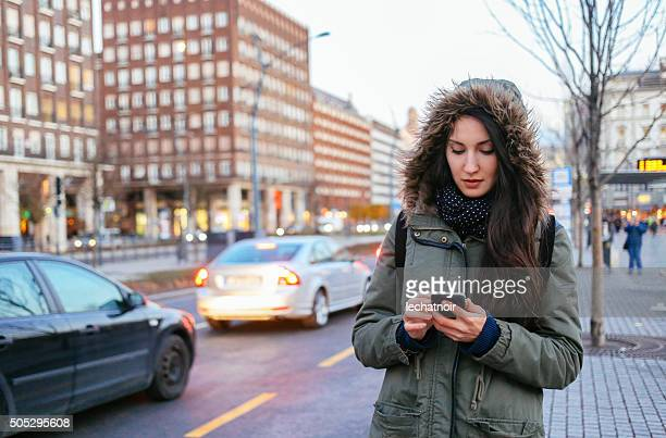 Winter portrait of a woman in the city calling taxi