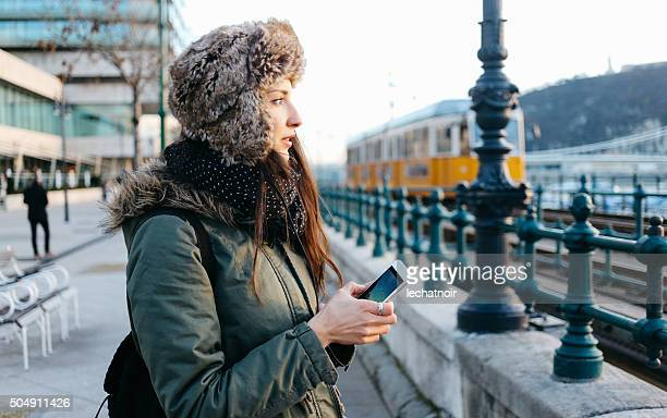 Winter portrait of a woman in the city using smartphone