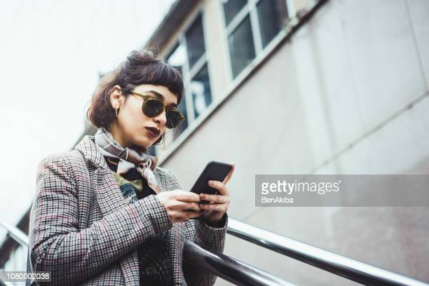 retrato de inverno de uma jovem mulher em mensagens de texto a cidade - echarpe - fotografias e filmes do acervo