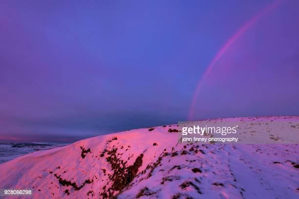 Winter rainbow at sunrise on Mam Tor, Derbyshire, UK