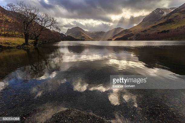 Winter reflections, shafts of sunlight break through clouds, Buttermere, Lake District National Park, Cumbria, England, United Kingdom, Europe