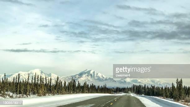 winter road y en alaska con montañas - paisajes de alaska fotografías e imágenes de stock