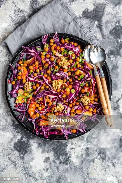 winter salad, red cabbage, roasted chickpea, blood orange, spring onion and walnut - rodekool stockfoto's en -beelden