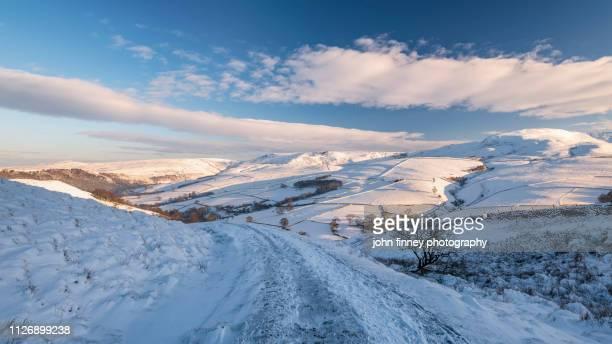 winter scene of kinder scout estate with golden light at sunrise. english peak district. uk - flanco de valle fotografías e imágenes de stock
