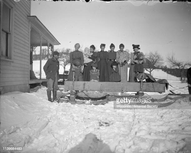 Winter scene with six women six children and a man examining a bobsled hitched to a horse Black River Falls Wisconsin 1900
