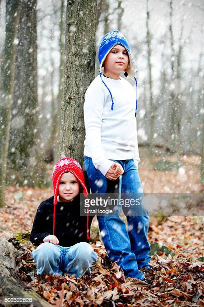 Winter scene with snow falling of two brothers outside