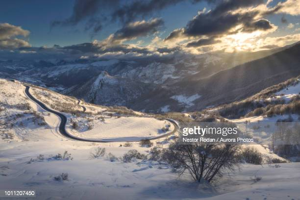 winter scenery with road and mountains, san glorio, liebana, cantabria, spain - レオン県 ストックフォトと画像