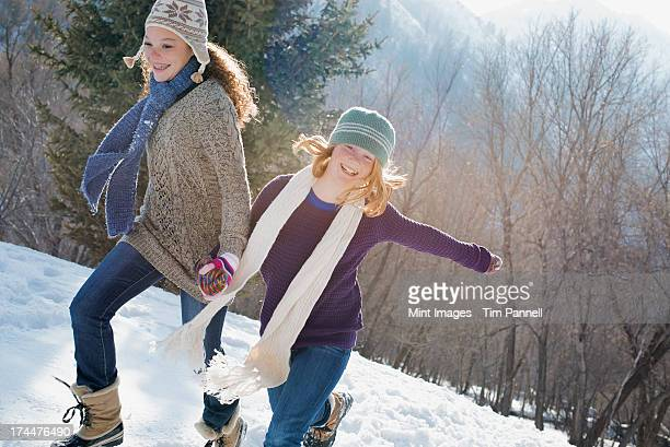 Winter scenery with snow on the ground. Two young girls hand in hand running across the snow.