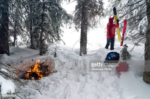 winter shelter with fire backcountry skiing - emergency shelter stock pictures, royalty-free photos & images