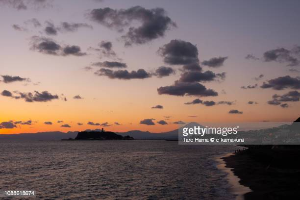 Winter snow-capped Mt. Fuji and Enoshima Island in the sunset in Japan