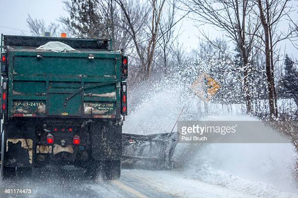 Winter snowplow and salt truck plows fresh snow from the boulevard and side of the road and spreads a layer of rock salt down in Peel region north of...