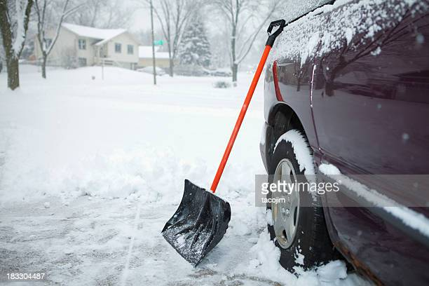 winter storm and snow shovel on driveway - snow shovel stock photos and pictures