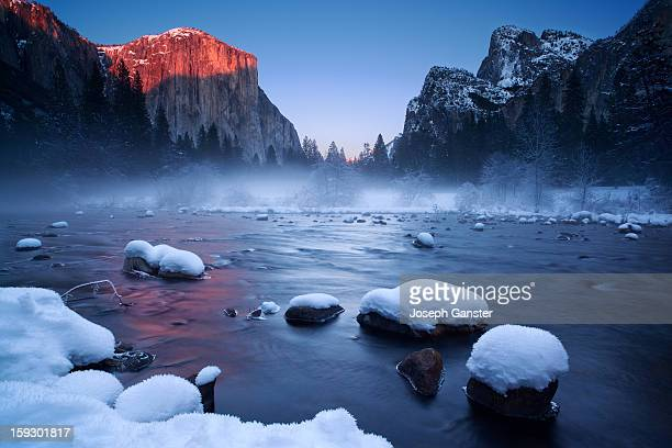 Winter sunset at The Gates of the Valley Yosemite National Park in the California Sierra The water of the Merced River reflected the alpenglow...