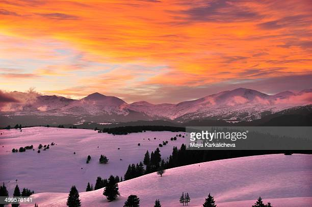 Winter sunset with red clouds in the mountains
