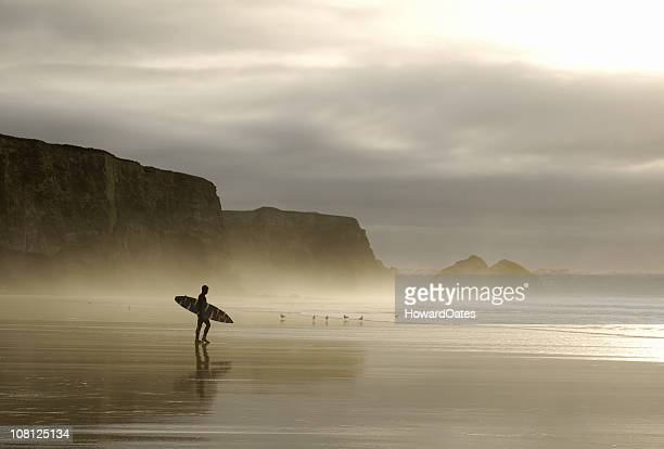 winter surfer walking through mist in cornwall - cornwall england stock pictures, royalty-free photos & images