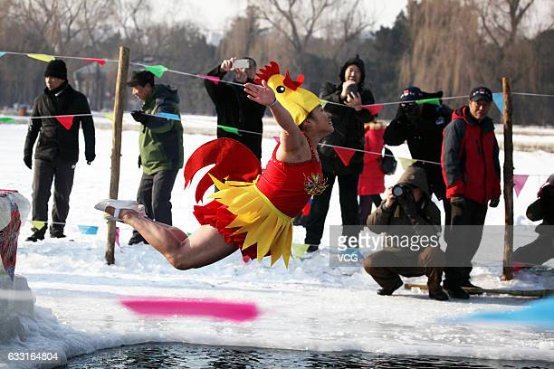 A winter swimmer wearing a chick hat jumps into water to celebrate the Year of the Rooster at Beiling Park on January 31 2017 in Shenyang Liaoning...