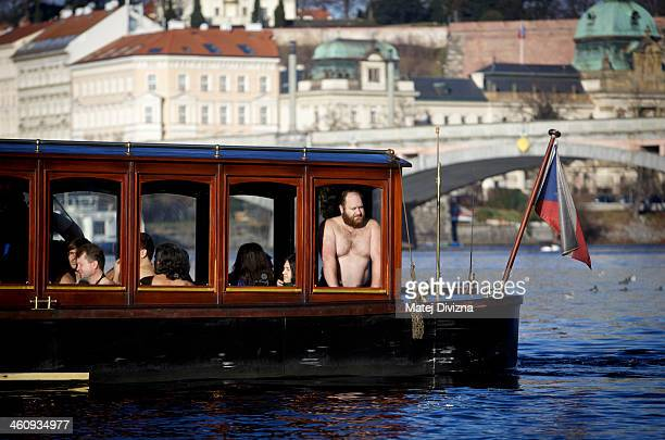 Winter swimmers arrive in the boat for the traditional Three Kings swim in the Moldau river on January 6 2014 in Prague Czech Republic About thirty...
