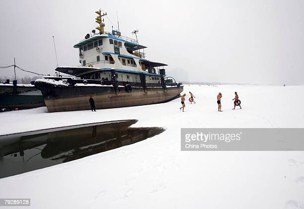 Winter swimmers walk past a stranded ship on the beach of the Yangtze River after snow on January 27 2008 in Wuhan of Hubei Province China Measured...